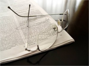Image of reading glasses on open newspaper